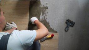 Installerend ceramische vloertegels - het meten en snijdend de stukken stock video