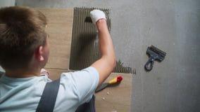 Installerend ceramische vloertegels - het meten en snijdend de stukken stock footage