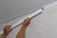 Installierung des Kronenformteils auf Decke in Raum mit gemalter Wand Fragment des Formteils, horizontale Ansicht Lizenzfreie Stockbilder