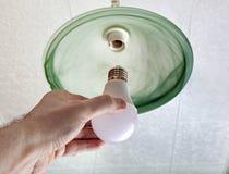 Installierung von Glühlampe LED in Deckenleuchte, Hand, die Lampe hält Stockfotos
