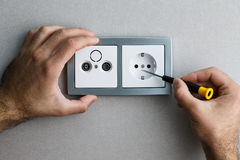 Installing AC power socket. Installing a silver wall-mounted AC power socket with a screwdriver on a grey wall, renovating home. Close up view Royalty Free Stock Photos
