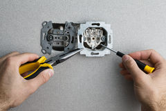 Installing AC power socket. Installing a wall-mounted AC power socket with a screwdriver on a grey wall, renovating home. Close up view stock photos