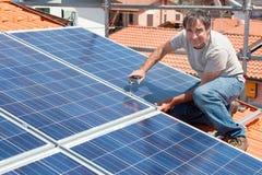Installing alternative energy photovoltaic solar panels. Man installing alternative energy photovoltaic solar panels on roof Royalty Free Stock Image
