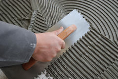 Installing Ceramic Tile. Man's hand spreading thinset mortar on cement board using notched trowel Royalty Free Stock Images