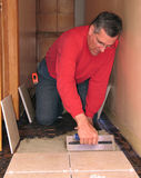 Installing ceramic tile. Man spreading mortar with trowel to install ceramic tiles Royalty Free Stock Photography