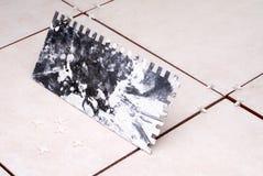 Installing ceramic tile. Notched trowel for installing new ceramic tile stock photography