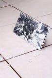 Installing ceramic tile. Notched trowel for installing new ceramic tile royalty free stock photos