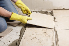 Installing ceramic tiles on a floor stock photo