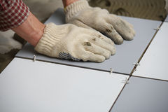 Installing ceramic tiles on a floor Stock Images