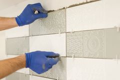 Installing ceramic tiles on the wall in kitchen. Placing tile spacers with hands, renovation, repair, construction.  royalty free stock photo