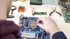 Installing CPU on blue motherboard. Engineer assembling CPU in repair shop stock footage