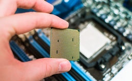 Installing the CPU into the motherboard. Engineer hand sets the processor to the motherboard Royalty Free Stock Photos