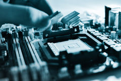 Installing the CPU into the motherboard. Hand sets the processor to the motherboard Stock Photography