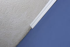 Installing crown molding on ceiling in room with painted wall. Fragment of molding, horizontal view. Stock Image