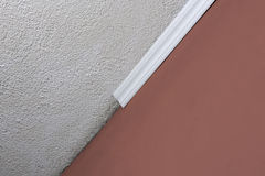Installing crown molding on ceiling in room with painted wall. Fragment of molding, horizontal view. Stock Photo