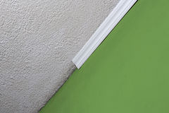 Installing crown molding on ceiling in room with painted wall. Fragment of molding, horizontal view. Royalty Free Stock Photos