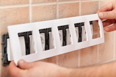 Installing decorative mask onto electrical wall fixture Stock Image