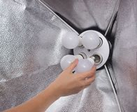Installing a diode energy saving light bulb in a soft box for lighting, hand, close-up, industry, electrician, electricity stock photos