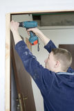 Installing the door. Construction joiner installs door. drilling the hole for screw Stock Image