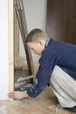 Installing the doors. Construction joiner installs door. drilling the hole for screw Royalty Free Stock Images