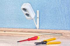 Installing of duplex receptacle outlet. Duplex power outlet with screwdriver and wire stripper cutter near it closeup house wall energy electricity work wood stock photo