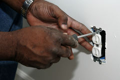 Installing an Electrical Outlet. A pair of Black hands using a screwdriver to install an electrical outlet stock photography