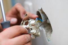 Installing an electrical plug / contact. A young electrician installing an electrical switch / plug in a new house royalty free stock photos
