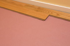 Installing Engineered Hardwood Floor. Series of shots of engineered hardwood floor being installed by a worker over pink felt paper using hand tools Stock Images