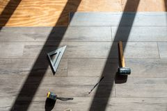 Installing engineered laminated wood flooring and tools to use royalty free stock photography