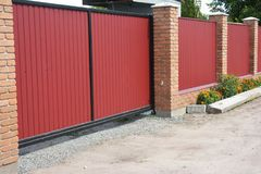 Installing house red metal fence with garage gate of modern style design. And flower bed Royalty Free Stock Image