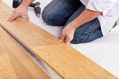 Installing laminate flooring. Fitting the next piece - focus on hand Royalty Free Stock Photography