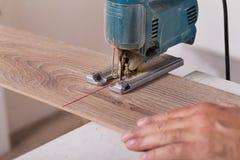 Installing laminate flooring. Carpenter cut parquet floor board Royalty Free Stock Images