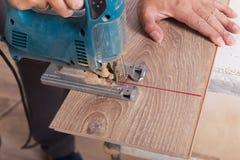 Installing laminate flooring. Carpenter cut parquet floor board Stock Image
