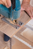 Installing laminate flooring. Carpenter cut parquet floor board Stock Photography