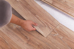 Installing laminate flooring. Carpenter lining parquet boards to Stock Photo