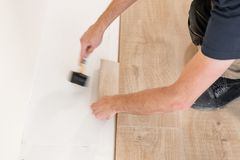 Installing laminate flooring fitting the next piece - focus on hand. Man laying laminate flooring. Male worker installing new wooden laminate flooring on a warm stock images