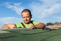 Installing the last strip of bitumen roof shingles Stock Image