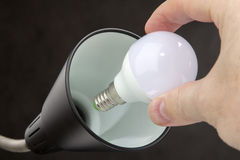 Installing LED lamp with lampshade Household lamps, black backgr Royalty Free Stock Photos