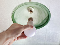 Installing LED light bulb in ceiling light, hand holding lamp. Close-up of energy-saving LED light bulb in the human hand, the replacement of the lamp in the Stock Photos