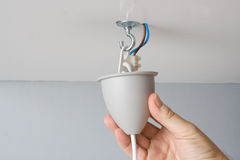 Installing a light fixture. Electrician installing a light fixture in a ceiling Royalty Free Stock Photo
