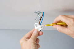 Installing a light fixture. Electrician installing a light fixture in a ceiling Stock Photography