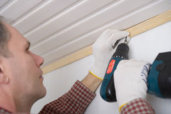 Installing molding to ceiling. Contractor installing molding to ceiling using cordless power screw driver Stock Image