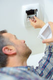 Installing motion sensor at home. Installing a motion sensor at home stock images