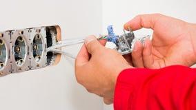 Installing Multiple Socket. Manual worker installing multiple socket on wall Royalty Free Stock Photo