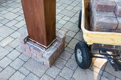 Installing a new brick pillar around a gazebo leg stock photography