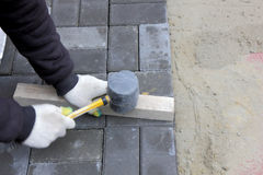 Installing paving slabs with a mallet Stock Photography