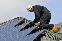 Installing Photovoltaic Panels. Solar Panel Installer on Residential Roof Royalty Free Stock Photos