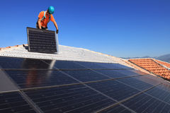 Installing photovoltaic solar panels. Man during intallation of alternative energy photovoltaic solar panels on roof Royalty Free Stock Photo