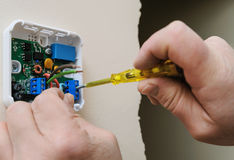 Installing a programmable room thermostat. Stock Photos