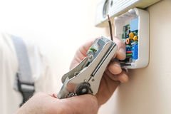 Installing a programmable room thermostat. Stock Images